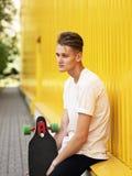 Individuo pensativo con un monopatín en un fondo borroso de la calle El inclinarse adolescente casual en una pared amarilla Conce Fotografía de archivo