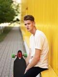 Individuo pensativo con un monopatín en un fondo borroso de la calle El inclinarse adolescente casual en una pared amarilla Conce Fotos de archivo