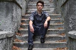 Individuo pensativo en la sentada gris en las escaleras grises imagenes de archivo