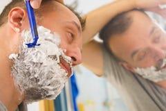Individuo que afeita su barba en cuarto de ba?o fotografía de archivo