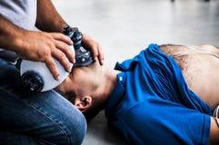 Individuo que ayuda a un hombre inconsciente Foto de archivo libre de regalías