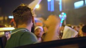 Individuo que baila cerca del coche con la muchedumbre Celebración atmosférica en honor de la victoria almacen de video