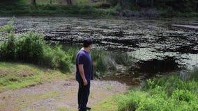 Individuo que camina cerca del lago almacen de video