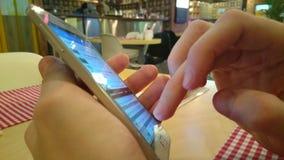Individuo que charla en línea, mandando un SMS, usando la conexión inalámbrica en el café metrajes