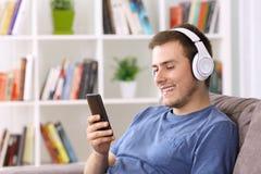 Individuo que escucha fluyendo música en casa Imagen de archivo