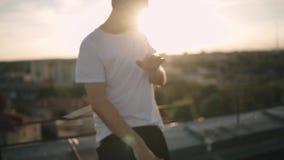 Individuo que escucha la música y que baila en el tejado Puesta del sol metrajes