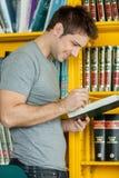Individuo que estudia con un libro Imagen de archivo