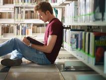 Individuo que estudia en biblioteca Foto de archivo