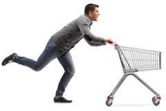 Individuo que funciona con y que empuja un carro de la compra vacío aislado en blanco Imagen de archivo libre de regalías