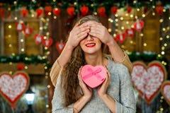 Individuo que hace sorpresa a su muchacha el día del ` s de la tarjeta del día de San Valentín Foto de archivo