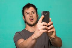 Individuo que hace un selfie con las caras divertidas Individuo que toma imágenes con su smartphone Imagen de archivo