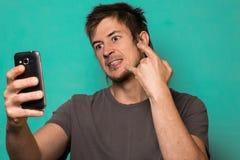 Individuo que hace un selfie con las caras divertidas Individuo que toma imágenes con su smartphone Imagen de archivo libre de regalías