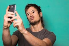 Individuo que hace un selfie con las caras divertidas Individuo que toma imágenes con su smartphone Fotos de archivo