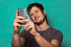 Individuo que hace un selfie con las caras divertidas Individuo que toma imágenes con su smartphone Foto de archivo libre de regalías