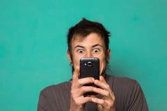 Individuo que hace un selfie con las caras divertidas Individuo que toma imágenes con su smartphone Fotografía de archivo