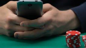 Individuo que juega el juego de azar el smartphone, el gastar dinero y el tiempo, app del póker almacen de video