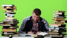 Individuo que lee y escribe los datos al cuaderno sí mismo Pantalla verde almacen de video
