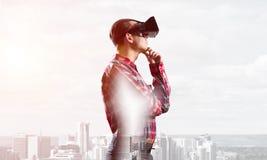 Individuo que lleva la camisa comprobada y la máscara virtual con la mano en la barbilla Fotos de archivo libres de regalías