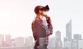 Individuo que lleva la camisa comprobada y la máscara virtual con la mano en la barbilla Foto de archivo