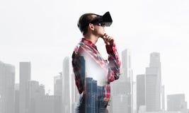 Individuo que lleva la camisa comprobada y la máscara virtual con la mano en la barbilla Fotografía de archivo