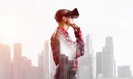 Individuo que lleva la camisa comprobada y la máscara virtual con la mano en la barbilla Imágenes de archivo libres de regalías