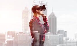 Individuo que lleva la camisa comprobada y la máscara virtual con la mano en la barbilla Fotos de archivo