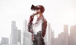 Individuo que lleva la camisa comprobada y la máscara virtual con la mano en la barbilla Imagen de archivo libre de regalías