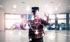 Individuo que lleva la camisa comprobada y la máscara virtual que alcanzan la mano al touc Fotos de archivo
