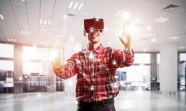Individuo que lleva la camisa comprobada y la máscara virtual que alcanzan la mano al touc Imagen de archivo