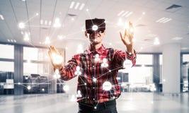Individuo que lleva la camisa comprobada y la máscara virtual que alcanzan la mano al touc Fotografía de archivo