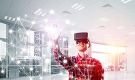Individuo que lleva la camisa comprobada y la máscara virtual que alcanzan la mano a la pantalla táctil Imagen de archivo