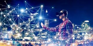 Individuo que lleva la camisa comprobada y la máscara virtual que alcanzan la mano a la sensación Foto de archivo libre de regalías