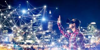 Individuo que lleva la camisa comprobada y la máscara virtual que alcanzan la mano a la sensación Imágenes de archivo libres de regalías