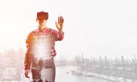 Individuo que lleva la camisa comprobada y la máscara virtual que estiran la mano para tocar algo Foto de archivo