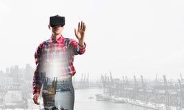 Individuo que lleva la camisa comprobada y la máscara virtual que estiran la mano para tocar algo Imagenes de archivo