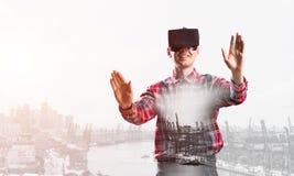 Individuo que lleva la camisa comprobada y la máscara virtual que estiran las manos y que intentan concentrar Fotos de archivo