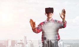 Individuo que lleva la camisa comprobada y la máscara virtual que estiran las manos y que intentan concentrar Fotografía de archivo libre de regalías