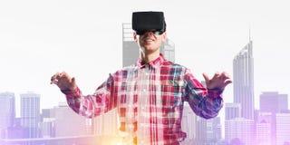 Individuo que lleva la camisa comprobada y la máscara virtual que estiran las manos y que intentan concentrar Imagen de archivo