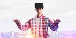 Individuo que lleva la camisa comprobada y la máscara virtual que estiran las manos y que intentan concentrar Foto de archivo libre de regalías
