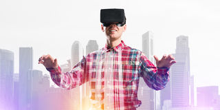 Individuo que lleva la camisa comprobada y la máscara virtual que estiran las manos y que intentan concentrar Fotografía de archivo