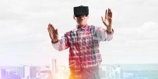 Individuo que lleva la camisa comprobada y la máscara virtual que estiran las manos y que intentan concentrar Imagen de archivo libre de regalías