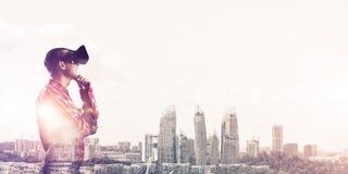 Individuo que lleva la camisa comprobada y la máscara virtual que llevan a cabo la mano en la barbilla Fotos de archivo libres de regalías
