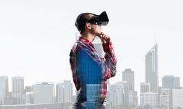 Individuo que lleva la camisa comprobada y la máscara virtual con la mano en la barbilla Imagenes de archivo