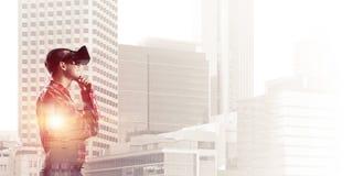 Individuo que lleva la camisa comprobada y la máscara virtual que llevan a cabo la mano en la barbilla Fotografía de archivo libre de regalías