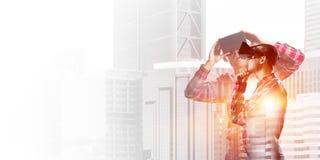 Individuo que lleva la camisa comprobada y la máscara virtual que llevan a cabo la mano en la barbilla Fotografía de archivo