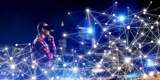 Individuo que lleva la camisa comprobada y la máscara virtual que llevan a cabo su mano en la barbilla Imagen de archivo