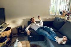 Individuo que miente en el sofá en casa que mira el teléfono celular imagen de archivo libre de regalías