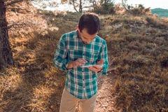 Individuo que mira su teléfono celular en el campo Fotografía de archivo