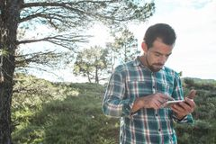 Individuo que mira su teléfono celular en el campo Fotografía de archivo libre de regalías