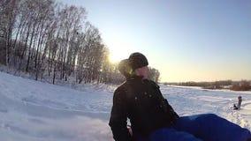 Individuo que monta una montaña nevosa, cayéndose  Cámara lenta Paisaje del invierno Nevado Deportes al aire libre almacen de metraje de vídeo